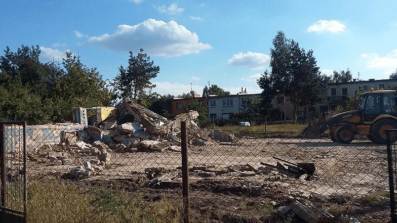 koparka spychająca pozostałości z rozbiórki budynku